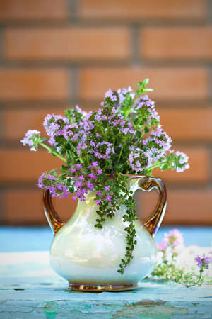 Flower bouquet in front of stone wall. Outdoor arrangement of flowers. Herbs thyme in vase