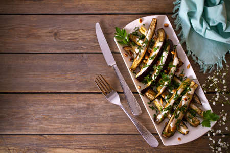 Eggplants or aubergines with yoghurt sauce, nuts and parsley. Overhead horizontal photo with copy space