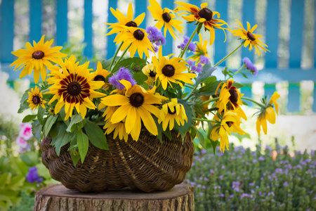Flower bouquet in vase in front of stone wall. Outdoor arrangement of flowers. Rudbeckia in basket