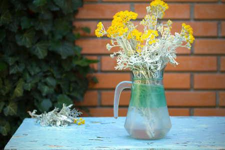 Flower bouquet in front of stone wall. Outdoor arrangement of flowers. Herbs in vase