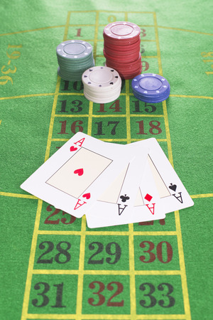 aces: Four aces and poker rooms on green carpet with numbers drawn Stock Photo