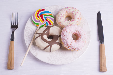 eating utensils: Multicolored lollipop with donuts and eating utensils