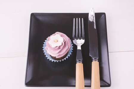 eating utensils: Cupcake and eating utensils on a black plate