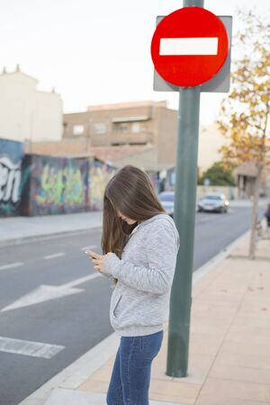 Teenager looking at mobile on a zebra crossing with a stop sign