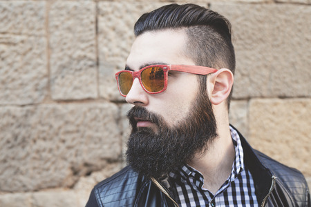 Closeup of a modern young man with red sunglasses. Hipster Archivio Fotografico
