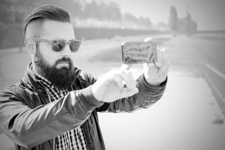 Hipster attractive modern man makes a selfie.. White and black
