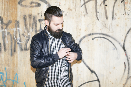 Modern and attractive man looking at his jacket