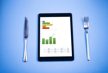 hostile: Tablet with colorful graphics finance with a knife and fork on blue background