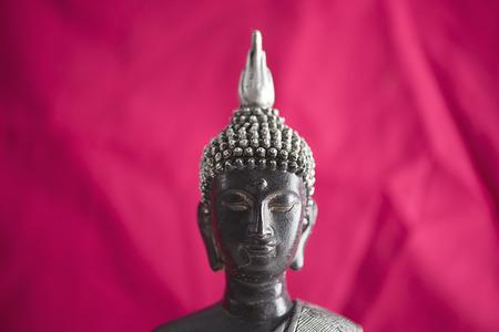 fondo rojo: la figura de Buda Colro gris y negro con el fondo de tela roja