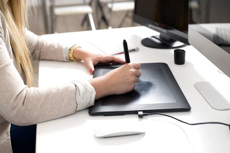 woman tablet: Woman hands using a graphics tablet in the office Stock Photo