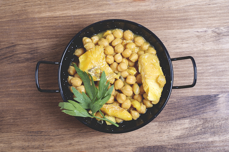 codfish: Healthy codfish with chickpeas in black saucepan. Stock Photo