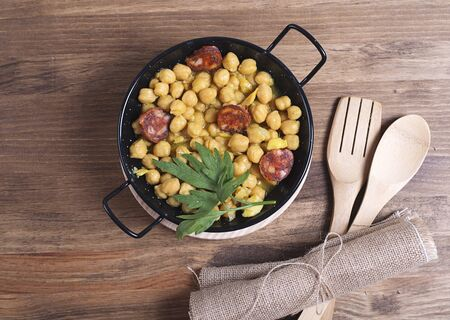 codfish: Close-up of nutritious chickpeas with codfish and sausage on plate.Fork and spoon.