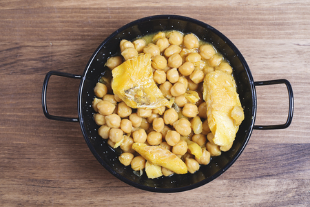 codfish: Healthy codfish with chickpeas in black saucepan.From above Stock Photo
