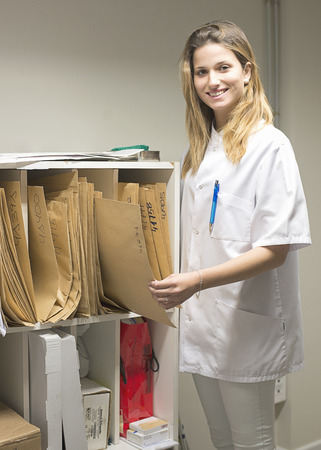 Attractive young doctor looks for a file in the closet