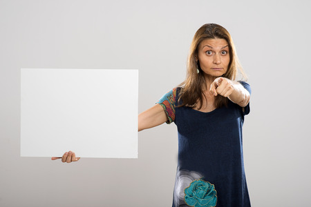 protruding eyes: Attractive woman with long hair pointing at the camera while holding a white poster