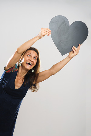 protruding eyes: Adult woman holds black heart and smiling