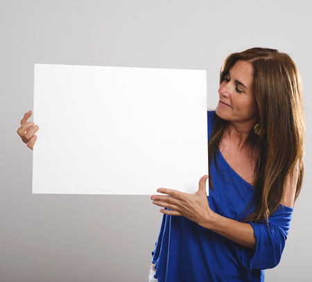 protruding eyes: Attractive woman with long hair smiling and holding a white poster