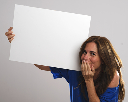 protruding eyes: Attractive woman with long hair covers her mouth and laughs With one hand while holding a white sign with the other hand Stock Photo