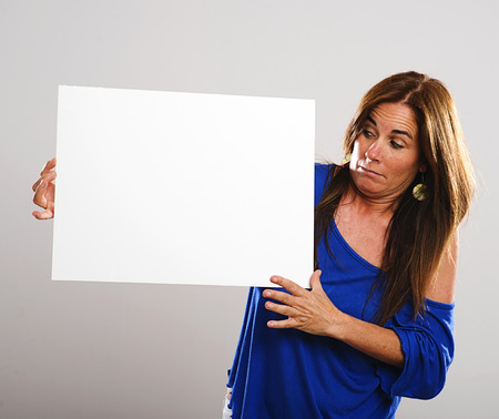 protruding eyes: Attractive woman with long hair and a look of surprise holding a white poster Stock Photo