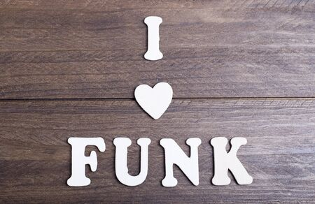 sonorous: White letters laying on dark wood messaging I love funk. Horizontal studio shot