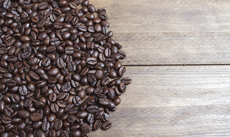 columbian: From above shot of handful of coffee beans on wooden table. Horizontal close up shot.  Stock Photo