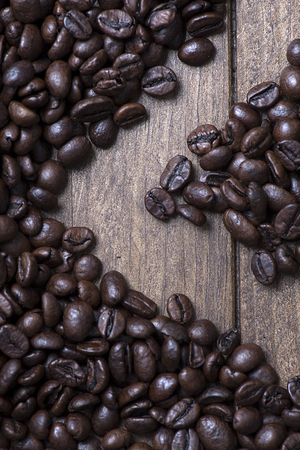 From above shot of handful of coffee beans on wooden table. Vetical close up shot.