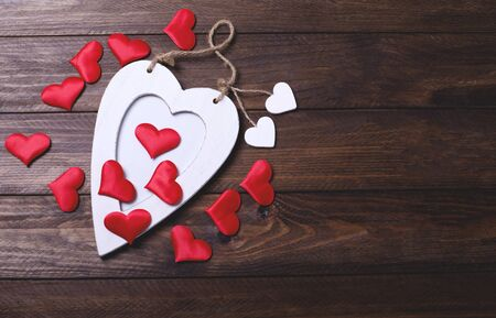 sweetie: White wooden heart with many red hearts on brown wooden table.  Stock Photo