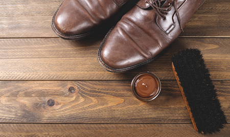 Top view of shoes and cleaning products on brown wooden table. Horizontal shoot.
