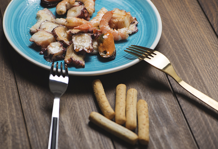 gave: Seafood salad next to bread sticks on wooden table. Horizontal shoot. Stock Photo