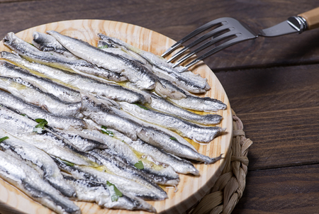 Tasty anchovies next to a fork on wooden table. Horizontal shoot.