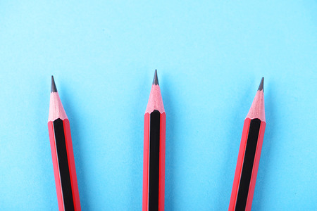 Three wooden pencils arranged on a blue background. Isolated.