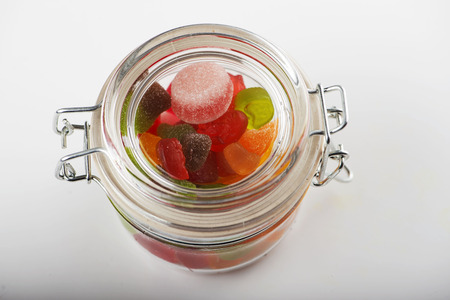 Glass jar full of sweets on white background.