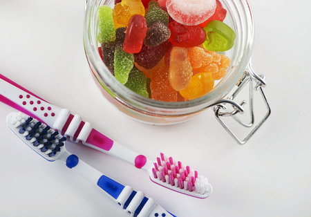 Glass jar full of goodies next to two toothbrushes on white background.