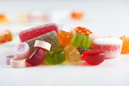 Close-up of candies and candies of various types and flavors on white background. Sweet.