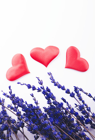 bunch of hearts: Three red hearts next to lavender flower on white background.  Stock Photo