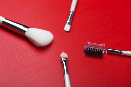 Top view of make-up utensils on red background. Horizontal shoot.