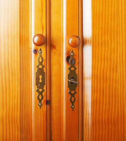 door knob: Door lock of a brown wooden closet.