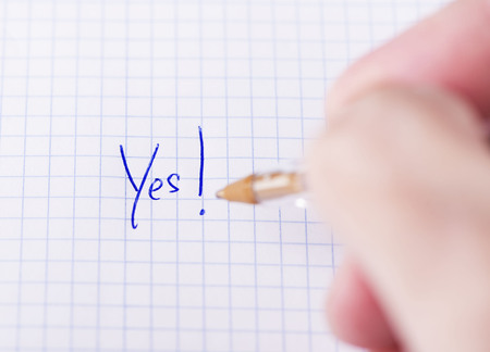 Male hand writes yes on sheet of paper. Stock Photo