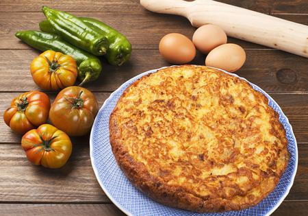 utensilios de cocina: Desde arriba utensilios de cocina, pimientos, huevos de tomates y aceite en la mesa de madera. Disparo horizontal.