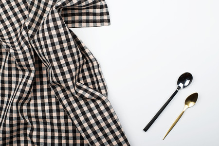 Background of plaid kitchen tablecloth and cutlery on white background. Copy space. Kitchen.