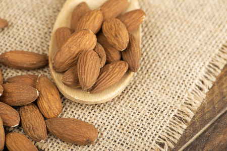 Close-up of almonds and wooden spoon on cloth. Food.