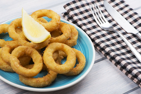 Close-up of platter of squids a la romana and a lemon on white wooden table next to a fork and a knife. Squids. Foto de archivo