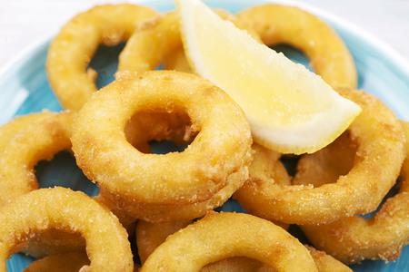 Close-up of a plate of squids a la romana and a lemon on blue plate. Squids. Horizontal shoot. Foto de archivo