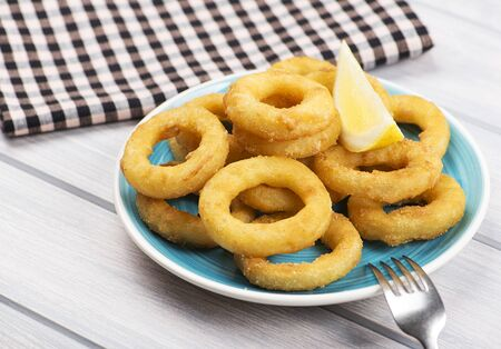 Close-up of a plate of squid a la romana, a lemon and a fork on blue plate. Squids. Horizontal shoot.