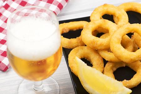 Close-up of a beer and a plate of squid a la romana, a lemon on a black plate. Squids. Foto de archivo