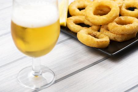 Beer glass next to squids a la romana on wooden board. Foto de archivo