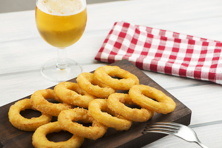 Close-up of a plate of squid a la romana on brown wooden board next to a beer, fork and napkin. Food squids. Foto de archivo