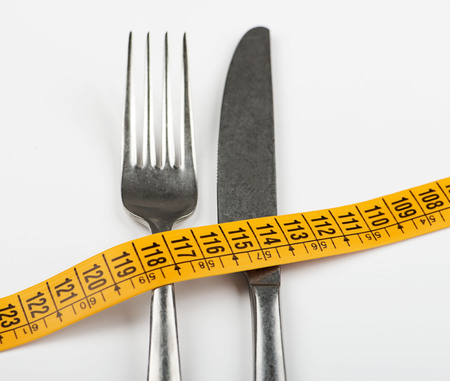 Tape measure on fork and knife. Concept of losing weight, diet.   Stock Photo