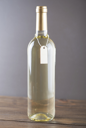 White wine bottle with a poster around on wooden background. Mockup. Vertical studio shot. Stock Photo