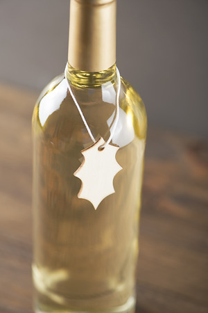 Close-up of white wine bottle with a poster around on wooden background. Mockup. Vertical studio shot.